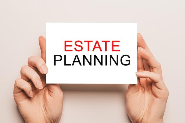 Vrouwelijke handen houden kaartpapier vast met de tekst estate planning op een oppervlak. zakelijk en financieel concept
