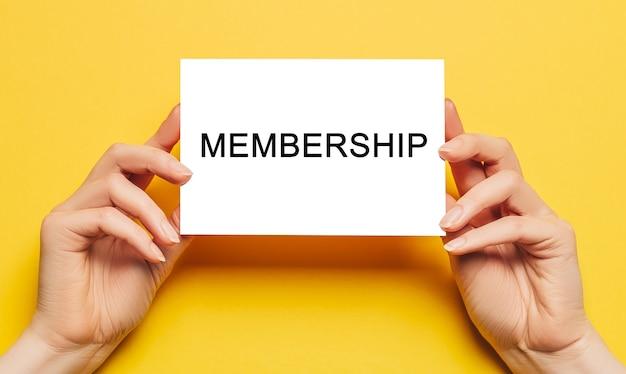 Vrouwelijke handen houden kaartpapier vast met de tekst lidmaatschap op een gele achtergrond. zakelijk en financieel concept