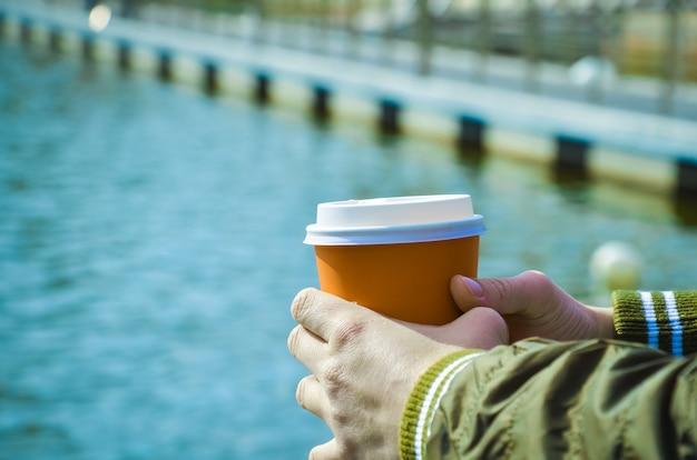 Vrouwelijke handen houden kartonnen beker met koffie op de achtergrond van de zee-pier. ontspanning aan zee, wandelingen langs de kust, koffie om mee te nemen. ruimte voor tekst. selectieve aandacht voor handen en kopje koffie