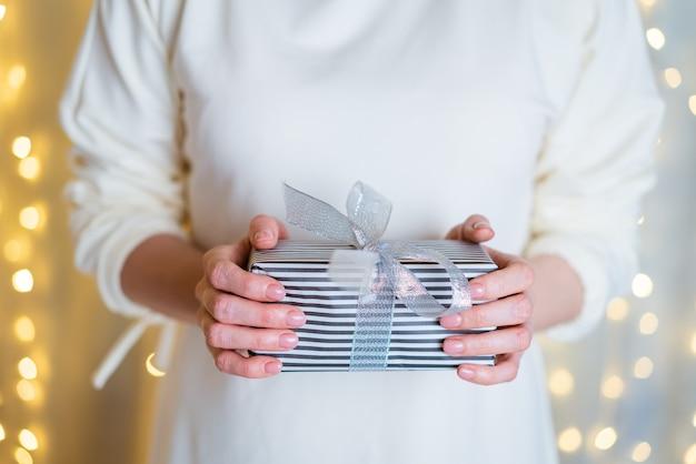 Vrouwelijke handen houden kerstmis of nieuwjaar geschenkdoos op boke achtergrond kerstmis nieuwjaar verjaardag conc...