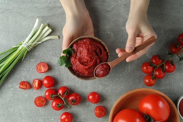 Vrouwelijke handen houden kom en lepel met tomatenpuree op grijze achtergrond met ingrediënten