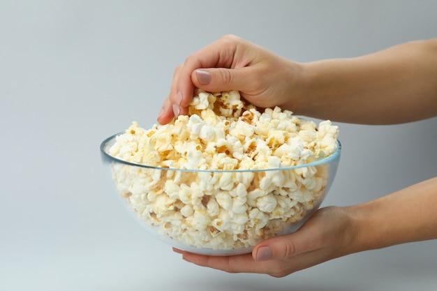 Vrouwelijke handen houden kom met popcorn op lichtgrijze achtergrond.
