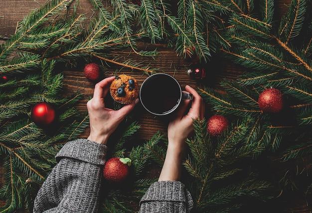 Vrouwelijke handen houden kopje thee en muffin naast de kerstboom op een tafel