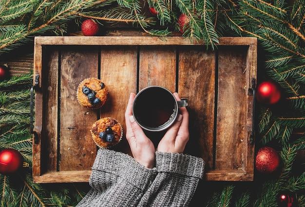 Vrouwelijke handen houden kopje thee naast kerstboom en muffins op een tafel