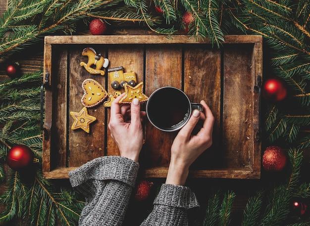 Vrouwelijke handen houden kopje thee naast koekjes en kerstboom op dienblad