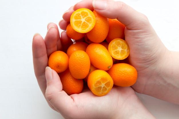 Vrouwelijke handen houden kumquats (mandarijnen) in de vorm van een hart op een witte achtergrond.