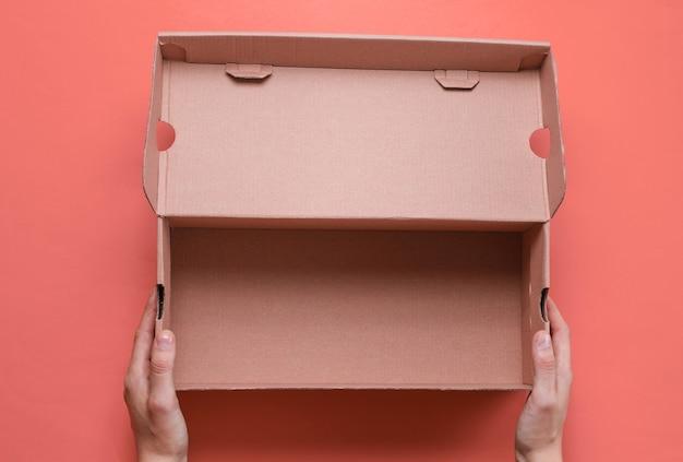 Vrouwelijke handen houden lege kartonnen doos op roze