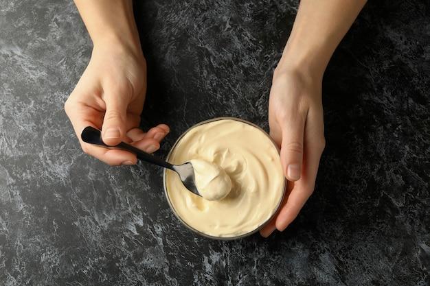 Vrouwelijke handen houden lepel en kom met mayonaise op zwarte smokey achtergrond