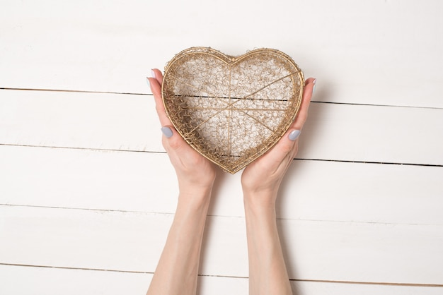 Vrouwelijke handen houden metaaldraad transparant hartvormig vak op een witte houten tafel