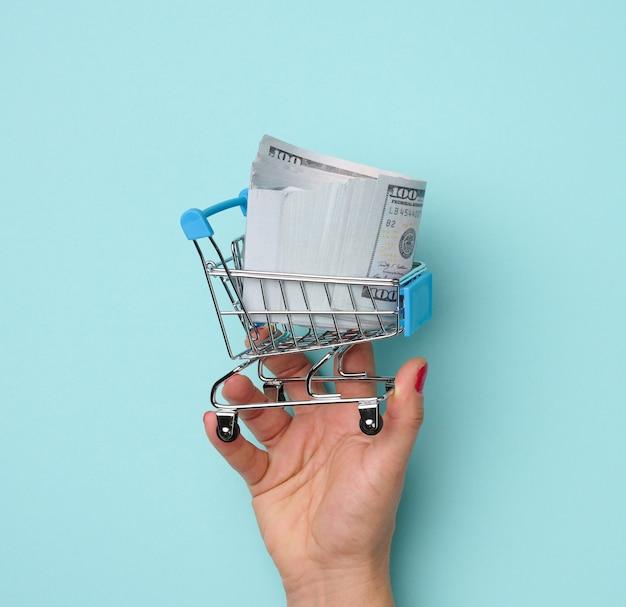 Vrouwelijke handen houden metalen miniatuur trolley met amerikaanse papieren dollars op een blauwe achtergrond. verkoopconcept, seizoenskortingen, kopieerruimte