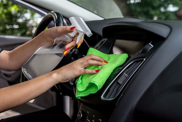Vrouwelijke handen houden microvezeldoek en spuitfles vast om de auto van binnen schoon te maken, close-up