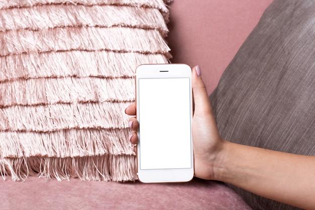 Vrouwelijke handen houden mobiele telefoon met wit scherm mock up op een roze interieur oppervlak