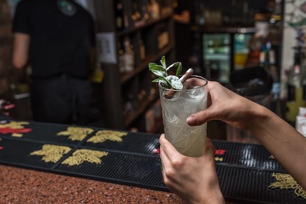 Vrouwelijke handen houden mojitococktail vast in een bar