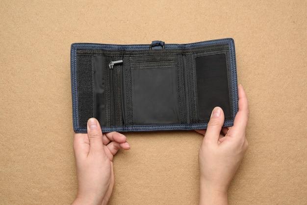 Vrouwelijke handen houden open lege blauwe textiel portemonnee op bruine achtergrond, bovenaanzicht