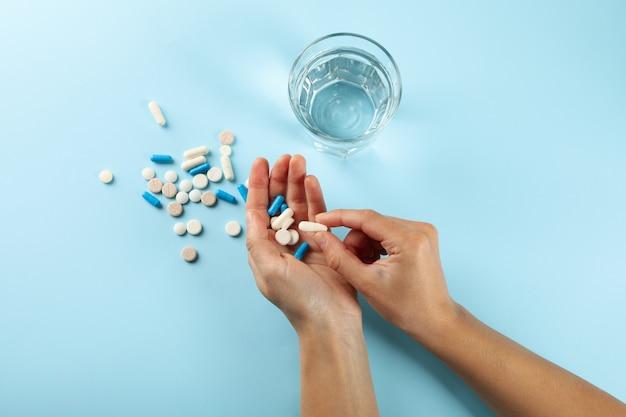 Vrouwelijke handen houden pillen op blauw met glas water