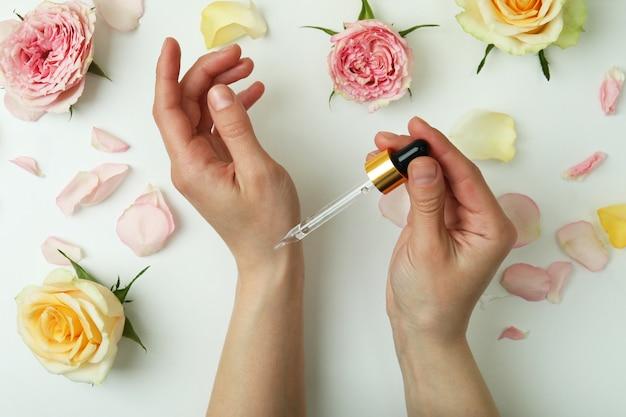 Vrouwelijke handen houden pipet vast met etherische olie van rozen