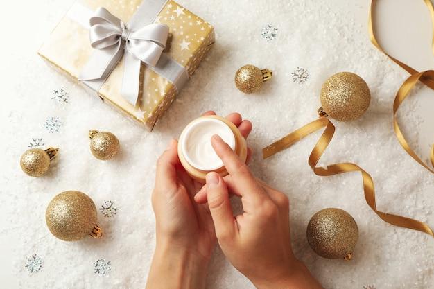 Vrouwelijke handen houden potje cosmetische crème op achtergrond met kerstaccessoires