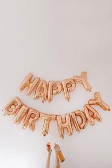 Vrouwelijke handen houden roze champagnefles en glas. rose gouden ballonnen happy birthday op witte muur. vakantie jubileumfeest vieren decoratie