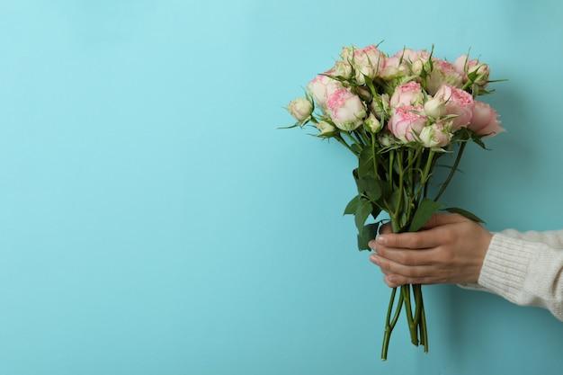 Vrouwelijke handen houden rozen op blauw