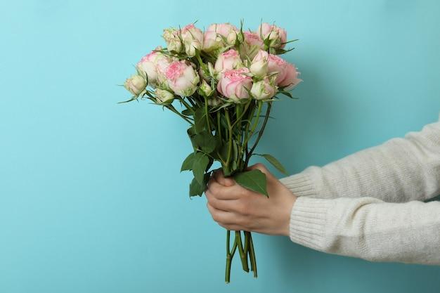 Vrouwelijke handen houden rozen op blauwe achtergrond