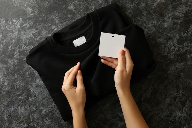 Vrouwelijke handen houden sweatshirt en tag op zwarte tafel