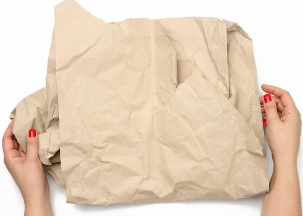 Vrouwelijke handen houden verfrommeld bruin papier op een witte achtergrond, bovenaanzicht