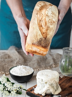Vrouwelijke handen houden vers gebakken brood en zuurdesem en ingrediënten voor het bakken van brood op een witte houten tafel