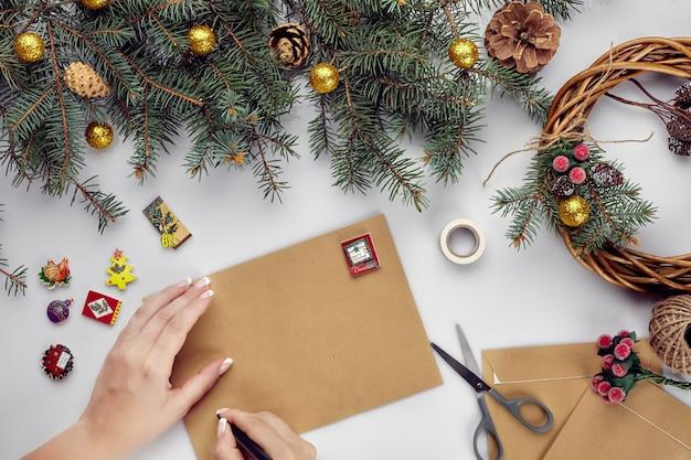 Vrouwelijke handen houden vrolijke kerstkaart en envelop kerstversiering achtergrond plat lag bovenaanzicht