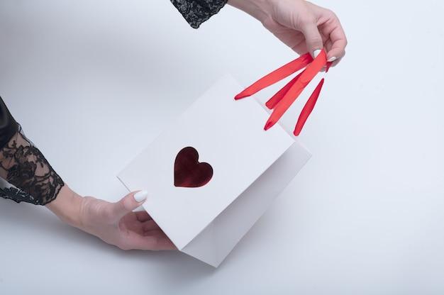 Vrouwelijke handen houden witte tas vast met een symbool in de vorm van een hart voor afhaalmaaltijden. op witte achtergrond.