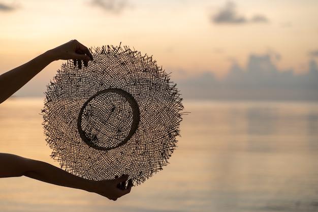Vrouwelijke handen houden zomer strooien hoed met uitzicht op de zonsondergang. vakantie concept