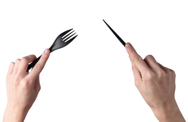 Vrouwelijke handen houden zwart plastic mes met een vork geïsoleerd op een witte ondergrond