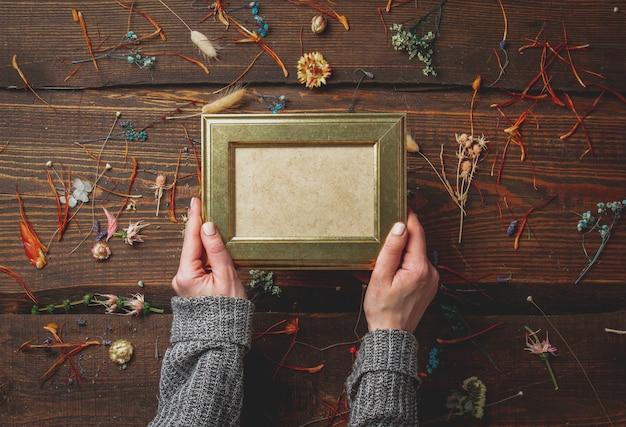 Vrouwelijke handen houdt fotolijst naast droge kruiden op houten tafel