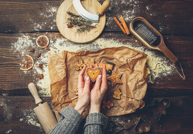Vrouwelijke handen houdt koekje naast bloem en papier op een tafel