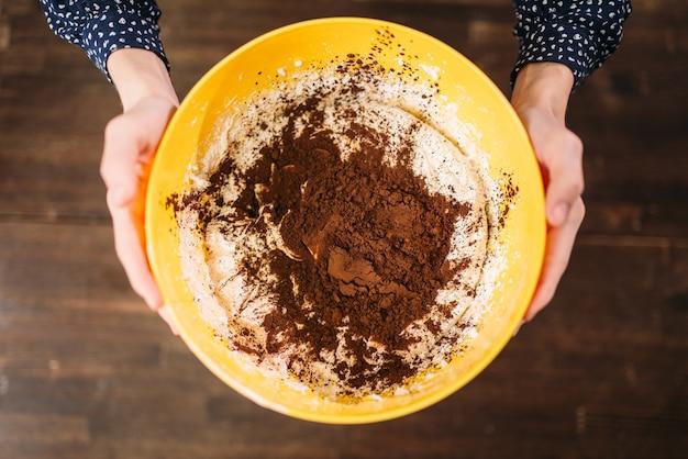 Vrouwelijke handen houdt kom met deeg en chocoladepoeder tegen op hout