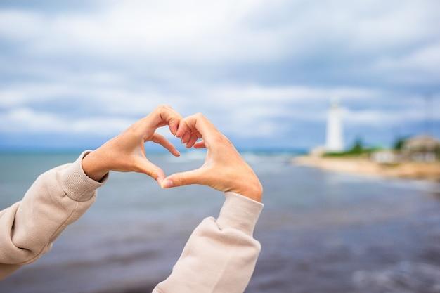 Vrouwelijke handen in de vorm van hart tegen de vuurtoren