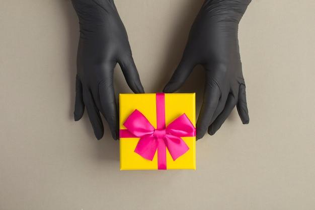 Vrouwelijke handen in een zwarte handschoenen met gele geschenkdoos op de grijze achtergrond