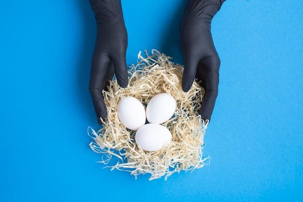 Vrouwelijke handen in een zwarte handschoenen withwhite kippeneieren in een nest