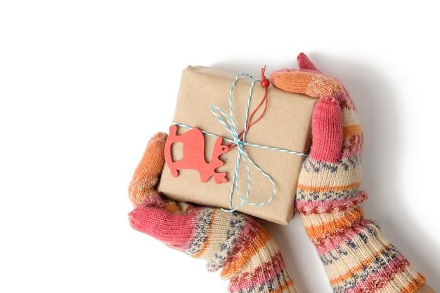 Vrouwelijke handen in gebreide wanten houden een doos verpakt in bruin papier en vastgebonden met een touw op een witte achtergrond, bovenaanzicht