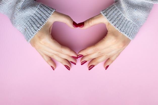 Vrouwelijke handen in grijze gebreide trui met bourgondische nagels hartsymbool maken op roze achtergrond