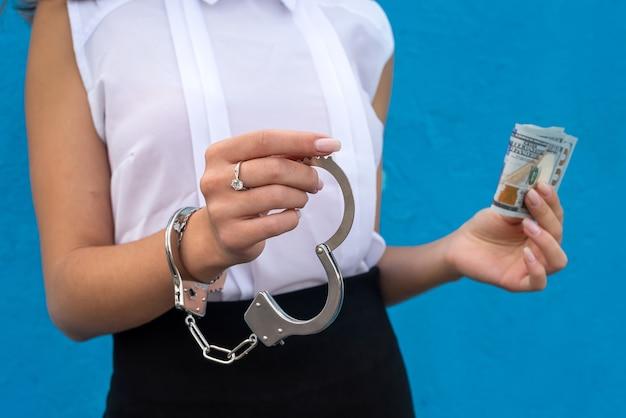 Vrouwelijke handen in handboeien houden ons geld vast. concept van illegale zaken., corruptie