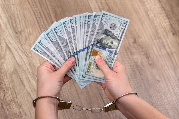Vrouwelijke handen in handboeien met dollars op tafel