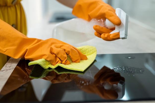 Vrouwelijke handen in handschoenen die het zwarte keukenoppervlak schoonmaken. huishoudelijk concept