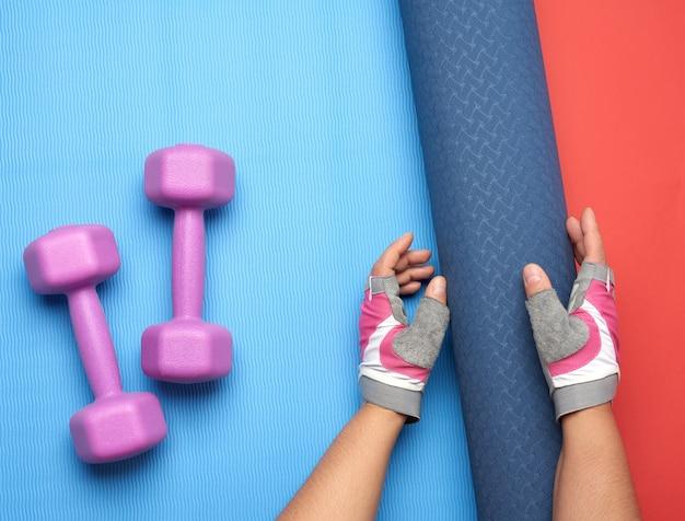 Vrouwelijke handen in sporthandschoenen ontvouwen een rode sportmat, bovenaanzicht.