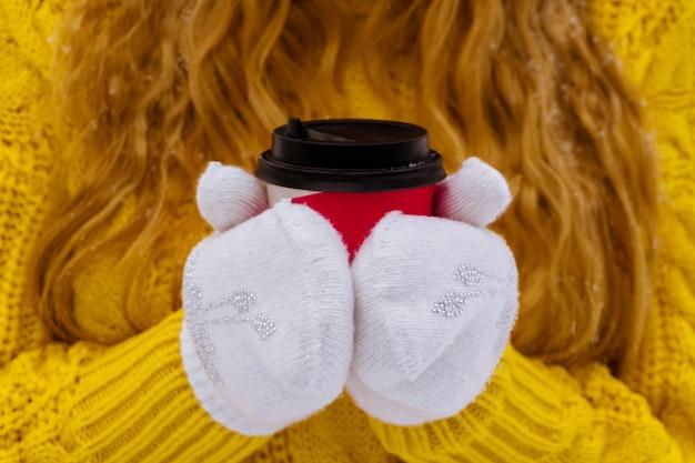 Vrouwelijke handen in wanten houden een papieren wegwerpkopje koffie van dichtbij vast