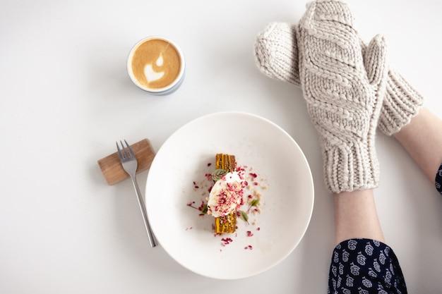 Vrouwelijke handen in witte wanten met cake en koffie op witte tafel met cake. concept van de winter, warmte, vakantie, evenementen.