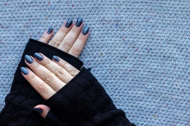 Vrouwelijke handen in zwarte gebreide handschoenen wanten met mooie manicure - donkerblauwe glinsterde nagels op gebreide achtergrond met kopie ruimte