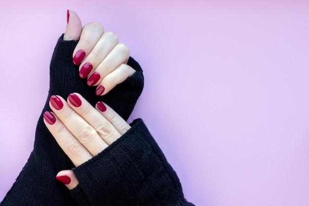 Vrouwelijke handen in zwarte gebreide handschoenen wanten met prachtige glanzende manicure - bordeaux, donkerrode kleur nagels op een roze achtergrond met kopie ruimte