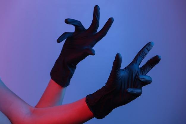 Vrouwelijke handen in zwarte latex handschoenen. gradiënt neonlicht