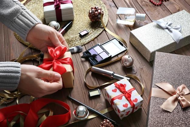 Vrouwelijke handen inpakken kerstcadeau en kleurrijke make-up cosmetica op houten oppervlak