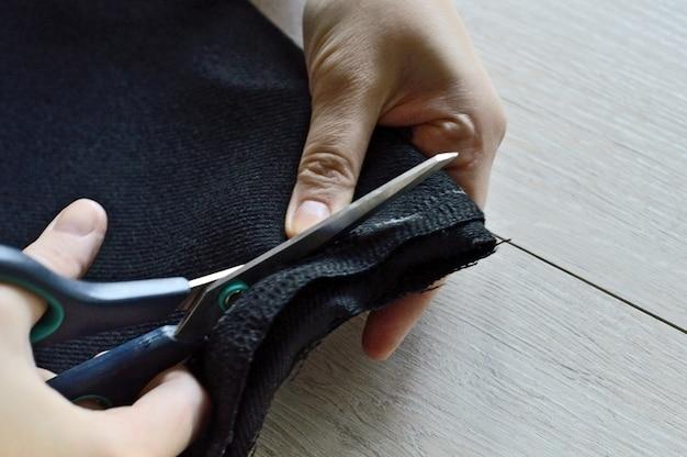 Vrouwelijke handen knippen de zwarte stof met een schaar. detailopname.